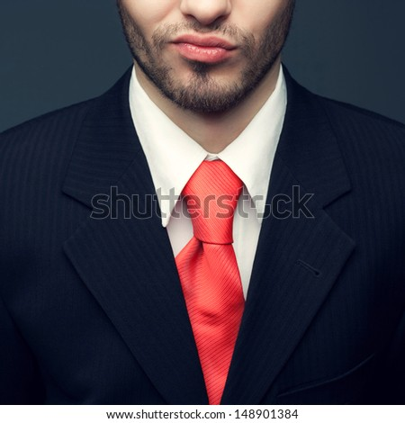 Seductive smile of a young handsome man (businessman) in classic black suit, white shirt with trendy pink tie. Close up. Studio shot - stock photo