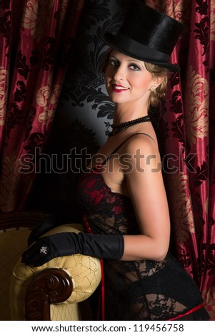 Seductive smiling woman in twenties vintage style with corset and top hat