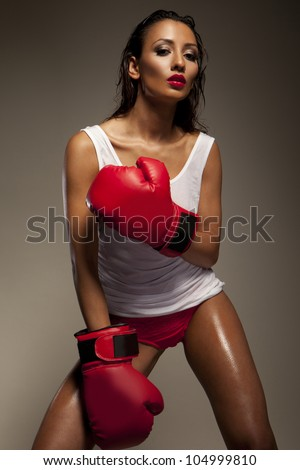 Seductive woman boxer glistens with sweat as she takes a break from traning at the gym - stock photo