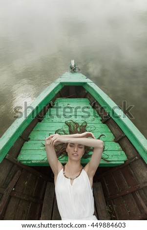 Seductive woman in the boat in the middle of nowhere