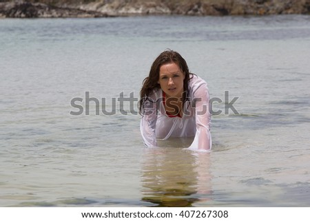 seductive woman in wet shirt crawling through the water at the sea - stock photo