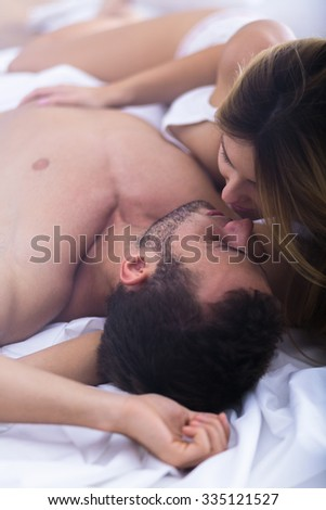 Seductive woman kissing his lover in bed