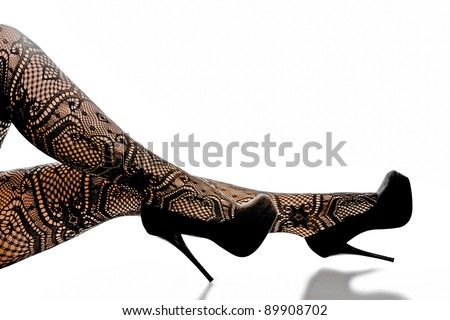 Seductive woman's legs wearing designer stockings and high heels. - stock photo