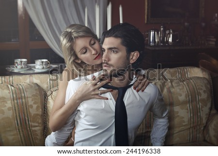 Seductive woman undressing elegant handsome man. Valentine day celebration - stock photo