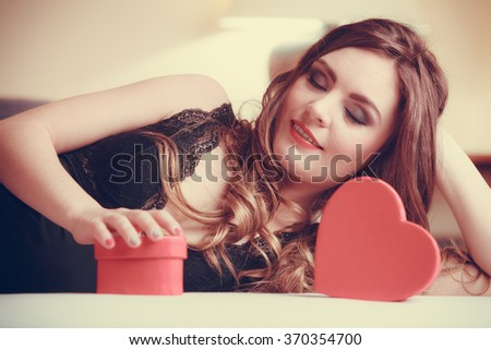 Seductive woman wearing lingerie in bed at home. Attractive sensual young girl with heart shape boxes. Female underwear fashion. Valentines day love. Instagram filter. - stock photo