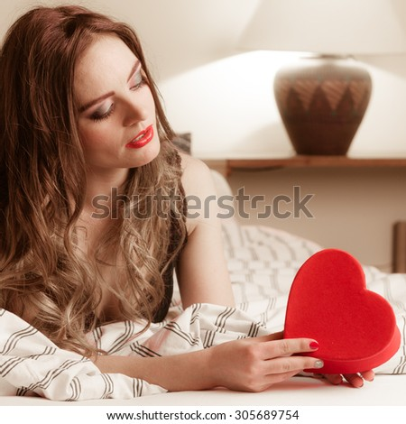 Seductive woman wearing lingerie in bed at home. Attractive sensual young girl with heart shape box. Female underwear fashion. Valentines day love. - stock photo