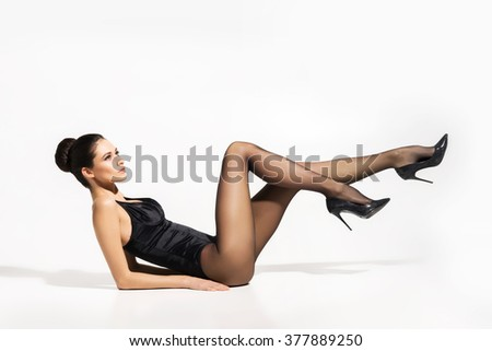 Seductive woman wearing pantyhose and heels with sexy legs up in the air over isolated background. - stock photo