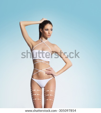 Seductive woman with arrows on body in underwear. Liposction concept. - stock photo