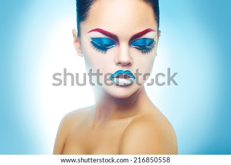 Seductive woman with healthy skin and make up on blue background in studio