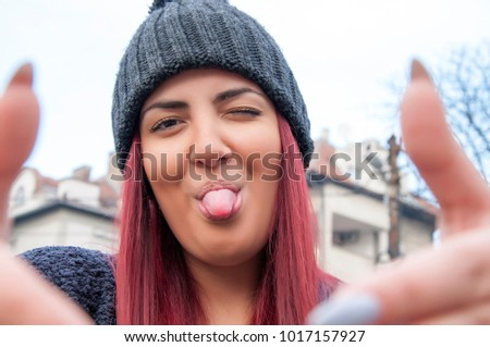 Seductive young redhead with woolen hat taking a selfie photo in the public park