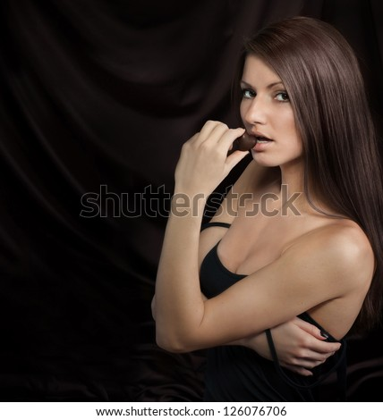 Seductive young woman biting chocolate candy, on dark background