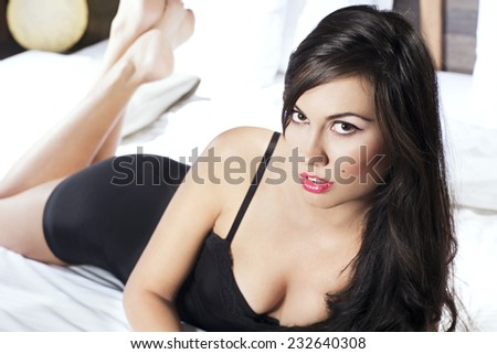 Seductive young woman in black nightie laying on the bed posing  - stock photo
