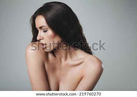 Seductive young woman topless on grey background. Sexy caucasian female model. - stock photo