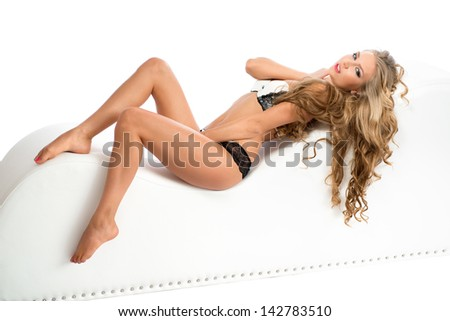 Seductive young woman with magnificent hair in lingerie lying on a chair over white background