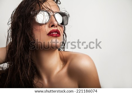 seductive young woman with red lips wearing modern sunglasses, studio white