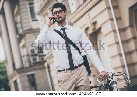 See you in office! Confident young man in glasses talking on mobile phone and holding hand on his bicycle while standing outdoors