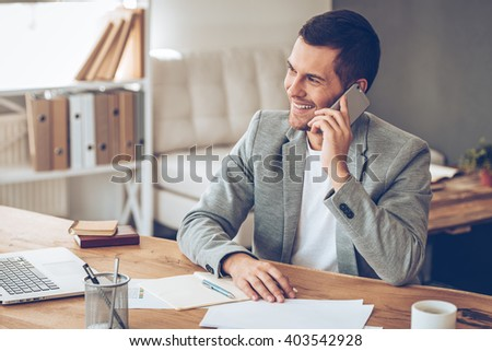 See you tomorrow! Handsome young man talking on mobile phone and looking away with smile while sitting at his working place  - stock photo