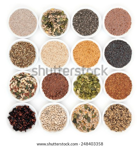 Seed and nut health food in porcelain bowls over white background. - stock photo
