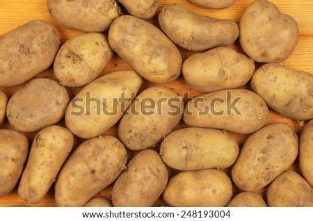 Seed potatoes on a wooden board - stock photo