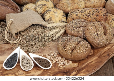 Seeded bread roll selection with wheat sheaths, rye grain in a hessian sack with chia, sunflower and caraway seed on an olive wood board. - stock photo