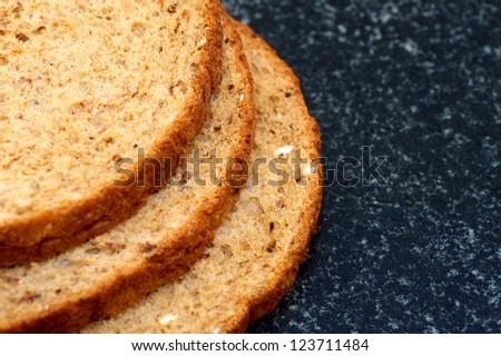 Seeded wholemeal bread (brown) on a granite chopping board - stock photo