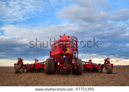 Seeding machine on the empty field at sunset - stock photo