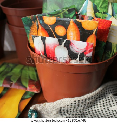 Seeds in packets in pot - stock photo