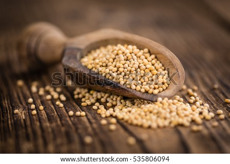 Seeds (Mustard) as high detailed close-up shot on a vintage wooden table (selective focus)