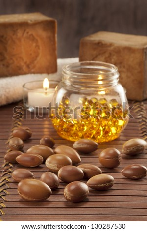 seeds of argan with yellow cosmetic pearl,light and soap - stock photo