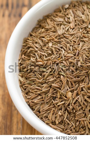 seeds of carum in white bowl on brown wooden background