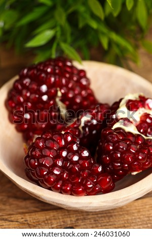 Seeds of grenadine in wooden plate, green leaves in the back - stock photo