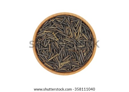 Seeds of wild rice in a wooden bowl on a white background