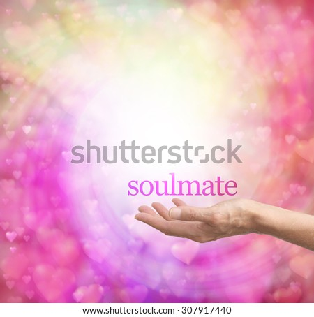 Seeking a soulmate - female hand palm up with the word soulmate floating above, surrounded by a spiral of pastel colored soft focus love hearts on a bokeh background - stock photo