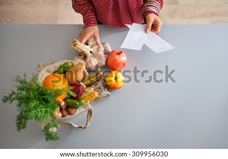 Seen from above, a burlap sac is full of fresh fall fruits and vegetables. A woman's elegant hands hold a bunch of fresh garlic and her shopping lists. - stock photo