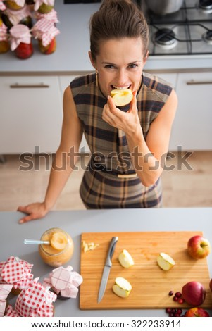 Seen from above, a happy woman smiles as she is biting into a freshly-cut apple. On the kitchen counter, a wooden cutting board with quartered apples. - stock photo