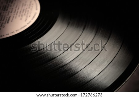 Segment of vinyl record with label showing the texture of the grooves, retro look