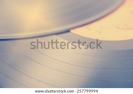 Segment of vinyl record with label showing the texture of the grooves, retro look, music background