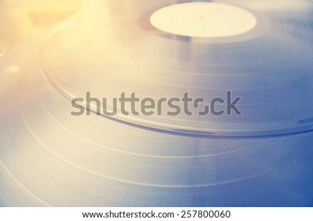 Segment of vinyl record with label showing the texture of the grooves, retro look, sun over vinyl, lifestyle positive photography - stock photo