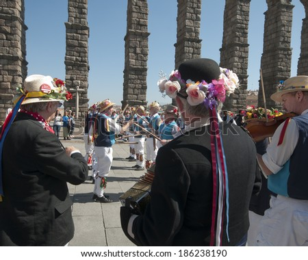 SEGOVIA  SPAIN - MARCH 16 2014 - East Suffolk Morris Men dancing in the Roman city of Segovia, Spain with blue and white uniform, bells and straw hats  with flowers.  Traditional English folk dancing.