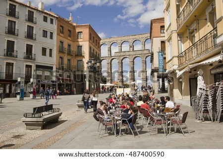 Segovia, Spain - May 30, 2016: People sit on a sidewalk cafe near the Roman aquaduct in the town of Segovia, Spain on May 30, 2016