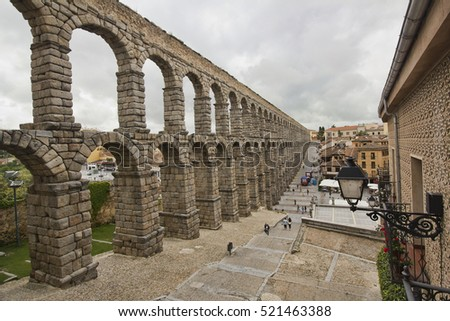 Segovia, Spain - May 30, 2016: People walk beneath the ruins of the roman aquaduct in Segovia, Spain on May 30, 2016