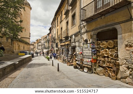 Segovia, Spain - May 30, 2016: People walk in the Callle de Marques del Arco with souvenir shops next to the cathedral in Segovia, Spain on May 30, 2016