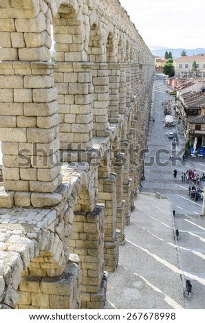 SEGOVIA, SPAIN - SEPTEMBER 20, 2014: A group of tourists in front of the Roman aqueduct in the city, heritage of humanity. - stock photo