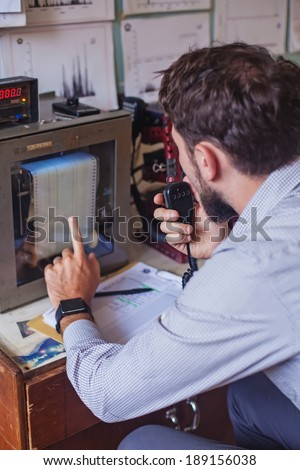 seismologist pointing at the equipment (soft focus on his hand) - stock photo
