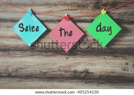 Seize the day on colorful paper with clothespin hanging on a string with wooden background, retro style. - stock photo