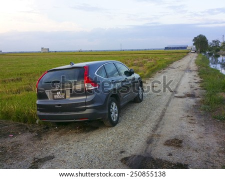 SEKINCHAN, SELANGOR, MALAYSIA-DECEMBER 11, 2014: An SUV Honda model CRV 2014 parks at paddy fields in Sekinchan, Selangor. This is the fourth generation of CRV produced by Honda Japan, Inc. - stock photo