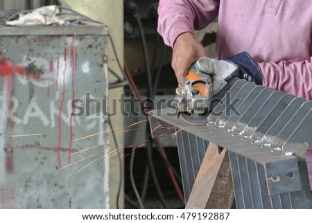 SELANGOR, MALAYSIA -AUGUST 29, 2016: Construction workers cutting reinforcement bar using mobile grinder at the construction site in Selangor, Malaysia.