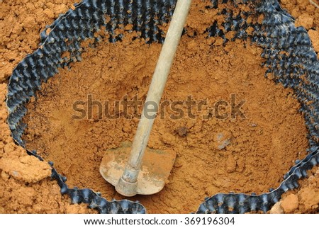 SELANGOR, MALAYSIA â?? DECEMBER 16, 2014: Hoe is used to filled soil into area that has been surrounded with a root barrier. - stock photo