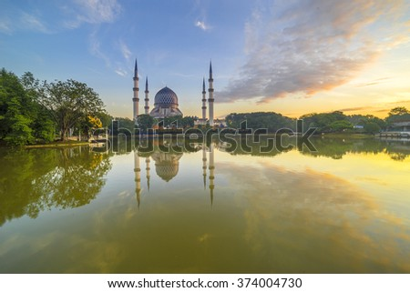 SELANGOR, MALAYSIA - JANUARY 30, 2016: The Beautiful Sultan Salahuddin Abdul Aziz Shah Mosque (also known as the Blue Mosque) with nature sunrise lighting and reflection. - stock photo