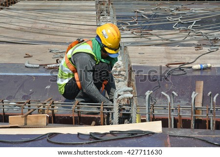 SELANGOR, MALAYSIA â?? MARCH 15, 2015: Construction workers cutting metal using mobile grinder at the construction site in Selangor, Malaysia.